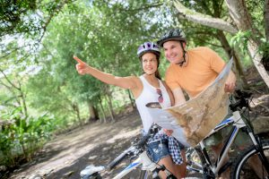 Couple mountain biking holding a map and pointing the right road - outdoors sports